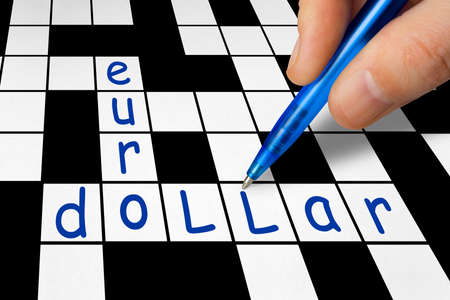 Hand filling in crossword - euro and dollar, business concept photo