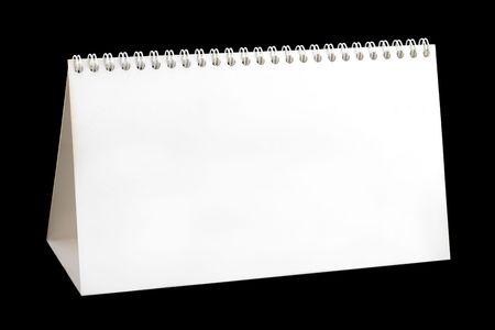 Blank desktop calendar, isolated on black background photo