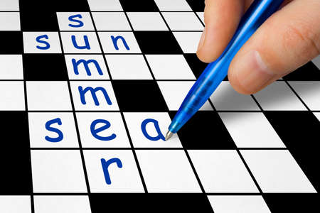crossword: Hand filling in crossword - summer vacation concept