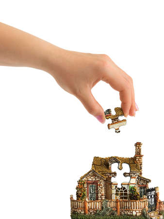 Hand and puzzle house isolated on white background photo