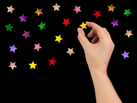 Hand put star to night sky isolated on black background photo