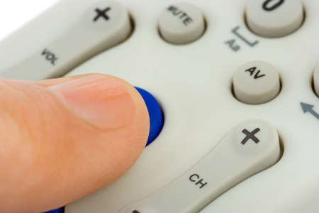 Hand pushing button on television remote control photo