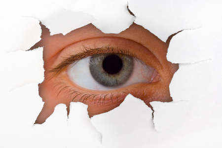 Eye looking through hole on paper surface Stock Photo - 3438067