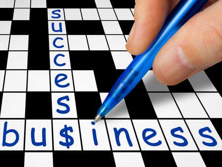 Hand filling in crossword - business and success photo