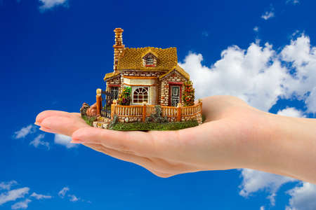Hand and house on sky background photo