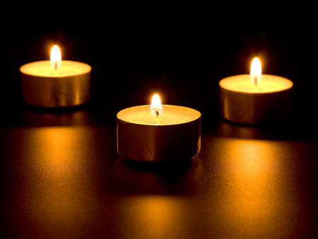 Three burning candles isolated on black background photo
