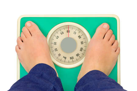 kilograms: Woman feet and weight scale isolated on white background