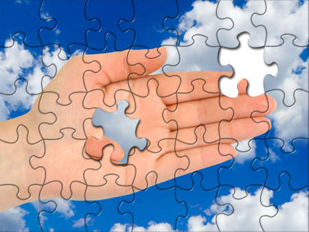 Puzzle hand without one piece, sky on background photo