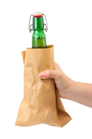 Hand and beer bottle in paper packet isolated on white background photo