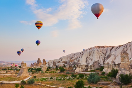 aeronautical: Hot air balloon flying over rock landscape at Cappadocia Turkey Stock Photo