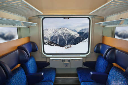 compartments: Interior of train and mountains in window - travel background