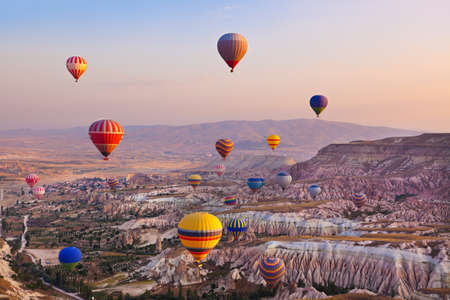 hot air balloon: Hot air balloon flying over rock landscape at Cappadocia Turkey Stock Photo
