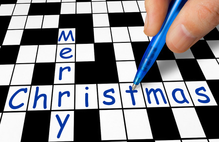 Hand filling in crossword - Merry Christmas - holiday concept photo