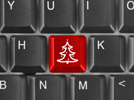 Computer keyboard with Christmas tree key - holiday concept photo