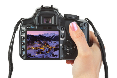 Camera in hand and winter Austria view isolated on white photo