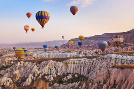 Hot air balloon flying over rock landscape at Cappadocia Turkey Stock Photo