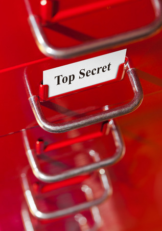 Red file cabinet with card Top Secret - business background photo