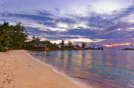 beach bar: Cafe on Seychelles tropical beach at sunset - nature background Stock Photo