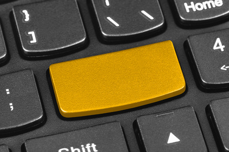 Computer notebook keyboard with blank yellow key - technology background photo
