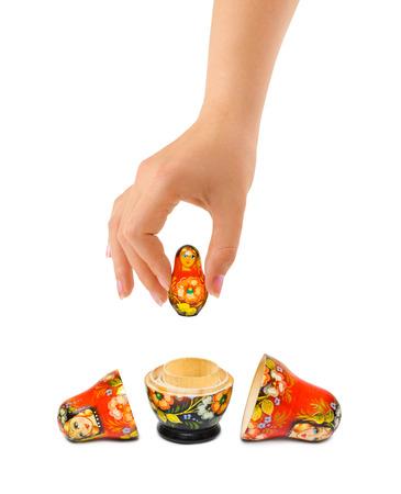 babushka: Hand and russian toy matrioska isolated on white background Stock Photo