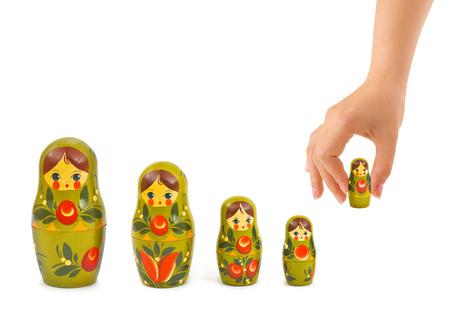 muñecas rusas: Mano y juguete ruso matrioska aislados sobre fondo blanco
