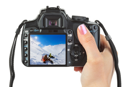 Camera in hand and winter Austria view (my photo) isolated on white background photo