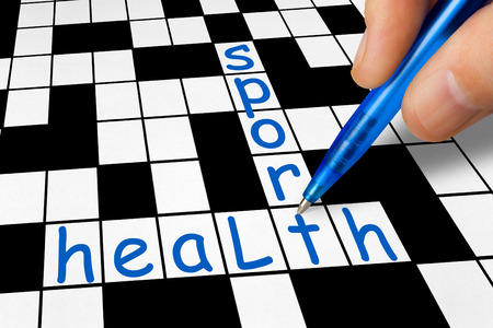 strong men: Hand filling in crossword - sport and health Stock Photo
