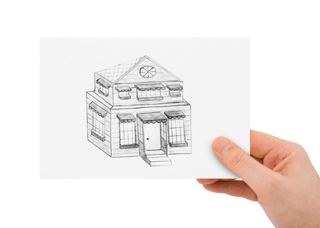 house drawing: Hand with drawing house isolated on white background