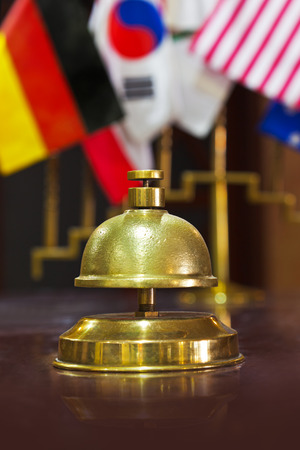 summon: Service ring bell on a hotel reception and flags on background