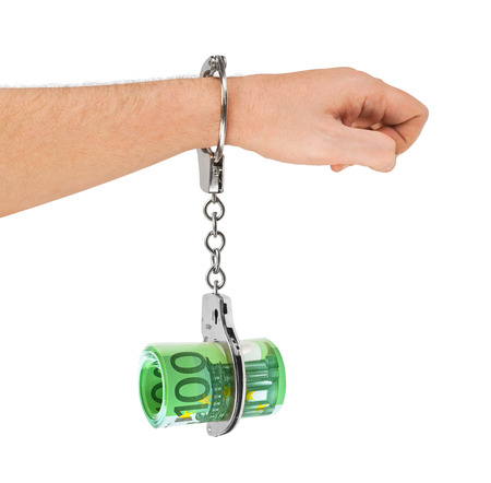 Hand with handcuffs and money isolated on white background photo