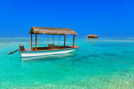 maldives island: Boat and bungalow on Maldives island - nature travel background