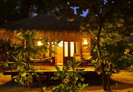 palapa: Beach bungalow at sunset - Maldives vacation background Editorial