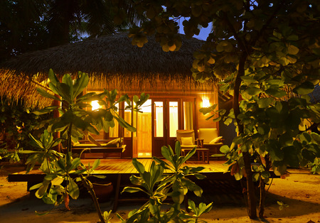 Beach bungalow at sunset - Maldives vacation background Editorial