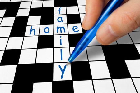 Hand filling in a crossword - family and home photo