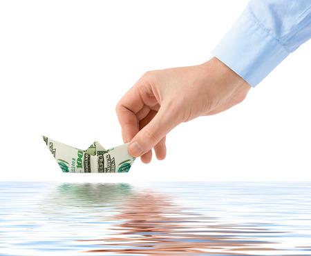 Hand launching money ship isolated on white background photo