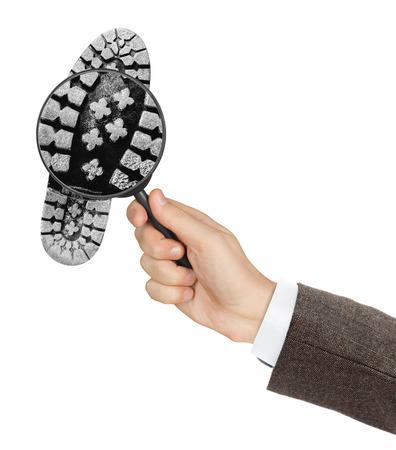 printout: Magnifying glass in hand and shoe printout isolated on white background