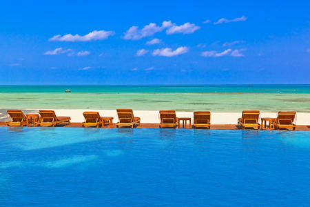 pool symbol: Loungers and pool on Maldives beach - nature vacation background Editorial