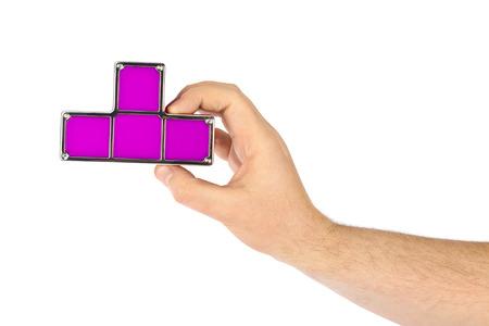 Hand with tetris toy blocks isolated on white background photo