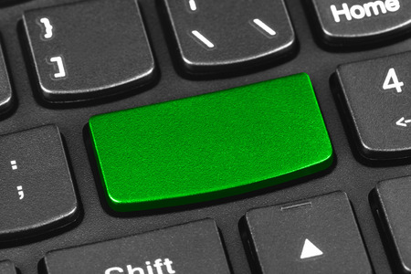 Computer notebook keyboard with blank green key - technology background photo