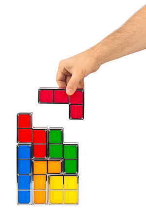 tetris: Hand with tetris toy blocks isolated on white background