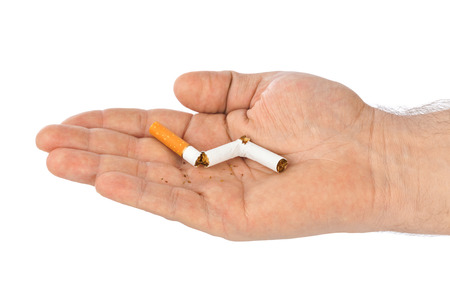 Broken cigarette in hand isolated on white background Stock Photo