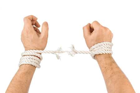 in bondage: Hands and breaking rope isolated on white background