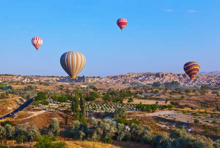 Hot air balloon flying over rock landscape at Cappadocia Turkey photo