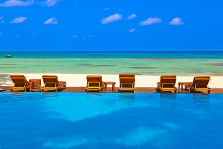 sunbed: Loungers and pool on Maldives beach - nature vacation background Stock Photo