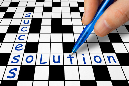 creative answers: Hand filling in crossword - Success and Solution Stock Photo