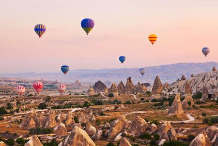 Hot air balloon flying over rock landscape at Cappadocia Turkey Stock Photo
