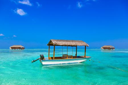 bungalow: Boat and bungalow on Maldives island - nature travel background