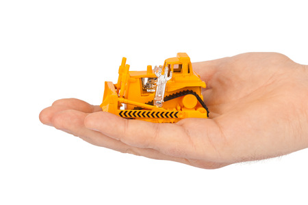 machine operator: Hand with toy bulldozer isolated on white background