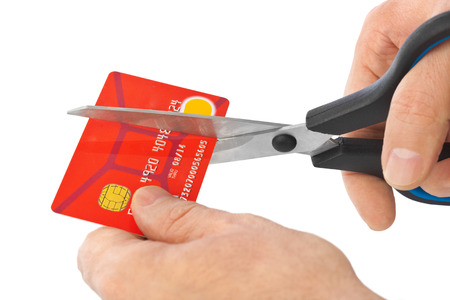 Scissors cutting old credit card isolated on white background photo