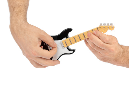 guitar tuner: Hands and toy electric guitar isolated on white background